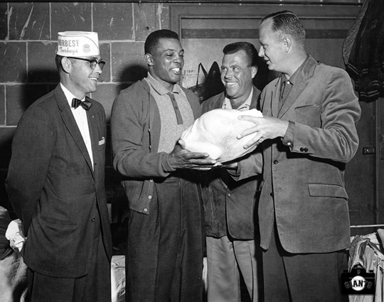 Willie Mays inspects a turkey