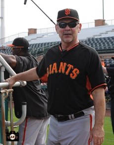 Bruce Bochy coaches at Scottsdale Stadium on Wednesday, February 19, 2014.