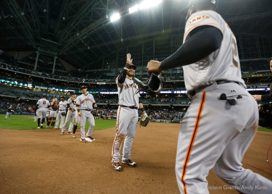 San Francisco Giants Brandon Crawford celebrates the Giants' 2-1 win over the Brewers with teammates.
