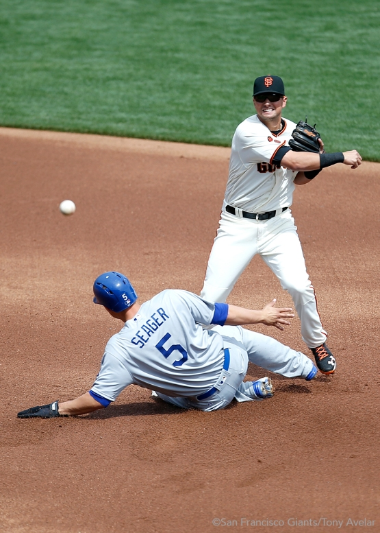 Joe Panik tags out Corey Seager and throws out Yasiel Puig during the first inning.