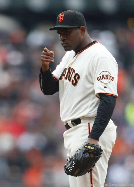 San Francisco Giants pitcher Santiago Casilla points to catcher Buster Posey during the 9-6 victory over the Dodgers.