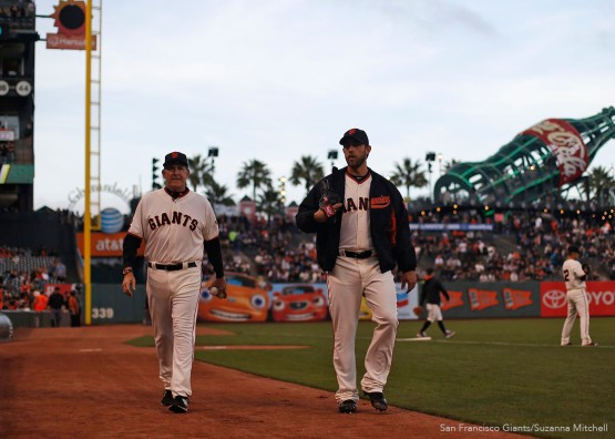 San Francisco Giants pitcher Madison Bumgarner and pitching coach Dave Righetti return to the dugout after warmups.