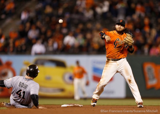 San Francisco Giants Brandon Crawford throws to first base after forcing out a Marlin.