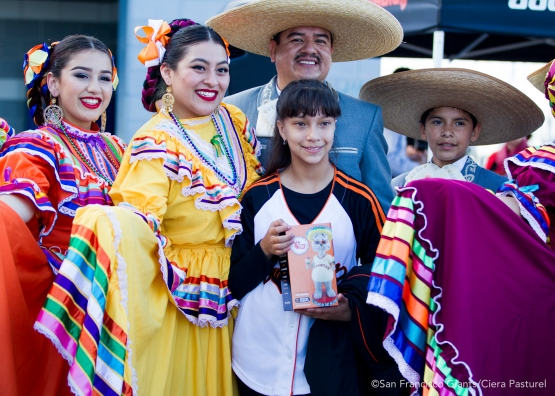 A SF Giants fan poses with dancers from Grupo Folklorico Los Laureles.