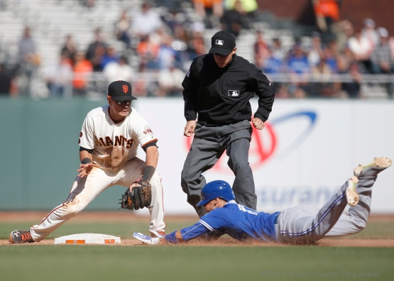 Joe Panik tags out Ryan Goins attempting to stretch a single into a double in the thirteenth inning.