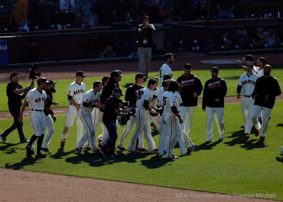 The Giants surround Buster Posey after he ended a thirteen inning game with a bases loaded walk.
