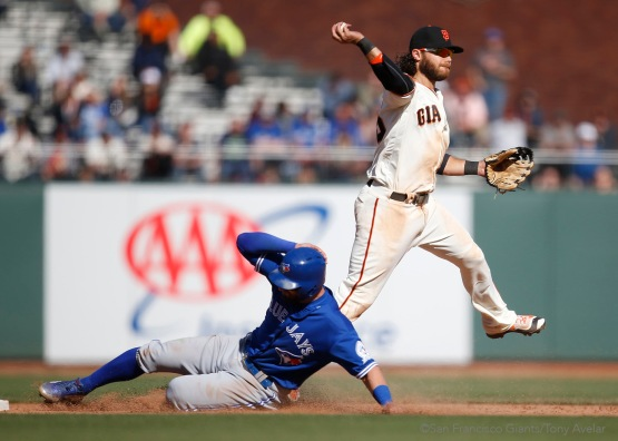 Brandon Crawford tags out Kevin Pillar and attempts to throw out Josh Donaldson in the thirteenth inning.