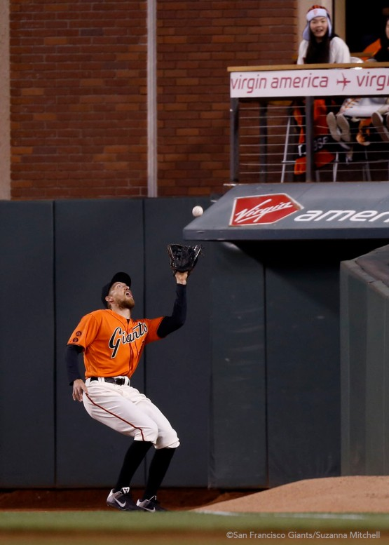 Hunter Pence catches a fly ball in foul territory hit by Javier Baez in the third inning.