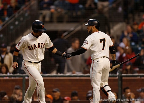 Joe Panik high fives Gregor Blanco after scoring on a walk drawn by Brandon Crawford.