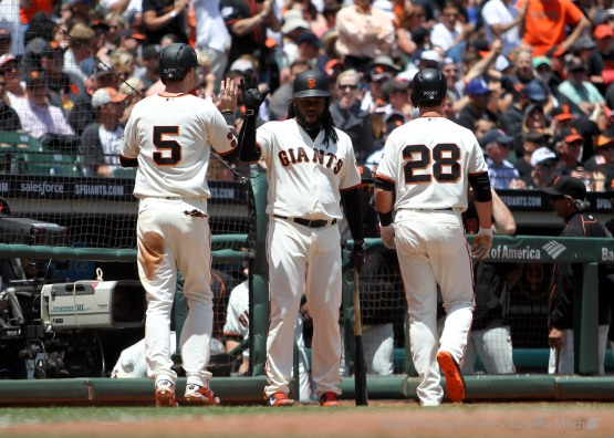Matt Duffy high fives Johnny Cueto after scoring on a fielder's choice hit into by Conor Gillaspie in the third inning.