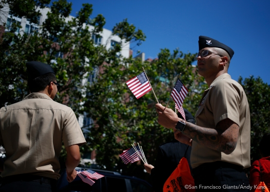 Members of the military collection donations for Operation Care and Comfort and pass out American flags.