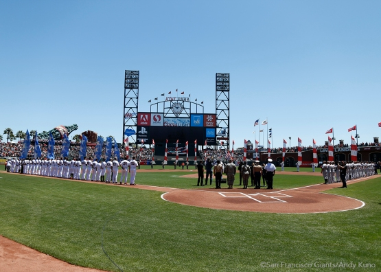 The Giants and the Rockies line up and observe the National Anthem.