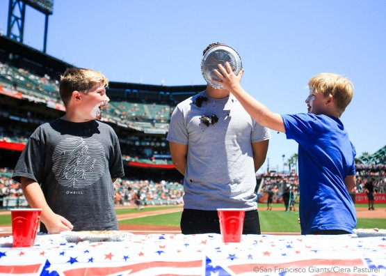 Three Giants fans participate in a pie eating contest before the game.