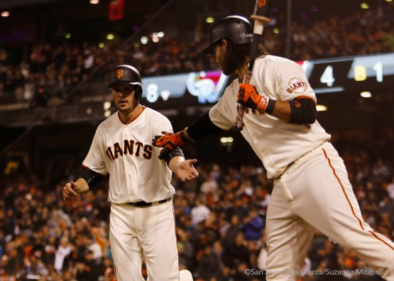 Grant Green high fives Brandon Crawford after scoring on a wild pitch in the eighth inning.