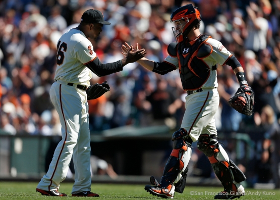 San Francisco Giants pitcher Santiago Casilla and catcher Buster Posey celebrate a Giants win.