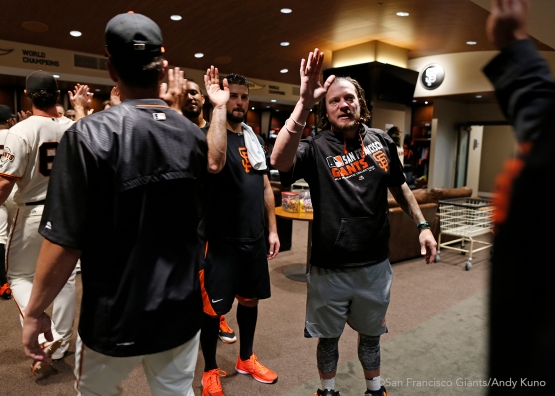 San Francisco Giants pitchers George Kontos and Jake Peavy give high fives inside the clubhouse.