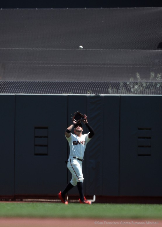 Gregor Blanco catches a fly ball in right field hit by Zack Cozart in the fourth inning.