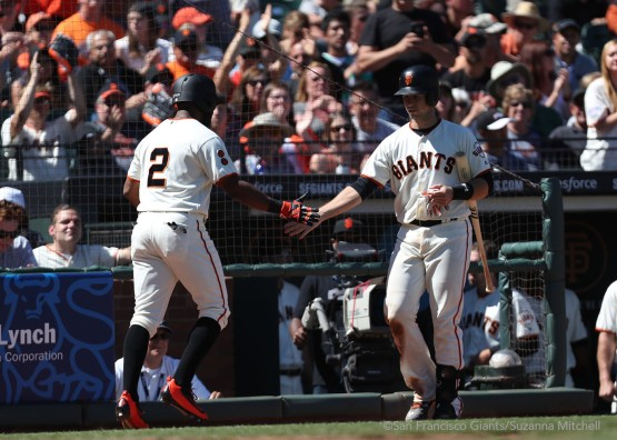 Denard Span high fives Buster Posey after scoring on a single hit by Angel Pagan in the seventh inning.