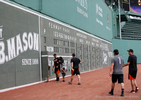 A handful of San Francisco Giants players enter the Green Monster at Fenway park.