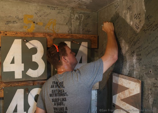 Matt Cain signs the wall inside the Green Monster at Fenway Park.