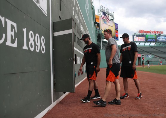Madison Bumgarner, Matt Cain and Derek Law go behind the Green Monster to sign the wall behind the Green Monster at Fenway Park.