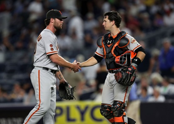 Hunter Strickland shakes hands with Buster Posey after pitching the twelfth inning.