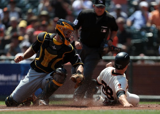 Buster Posey slides safely home in the first inning on a double hit by Brandon Crawford.