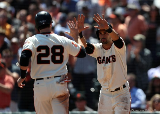 Buster Posey and Angel Pagan high five after scoring on a triple hit by Brandon Crawford in the fourth inning.