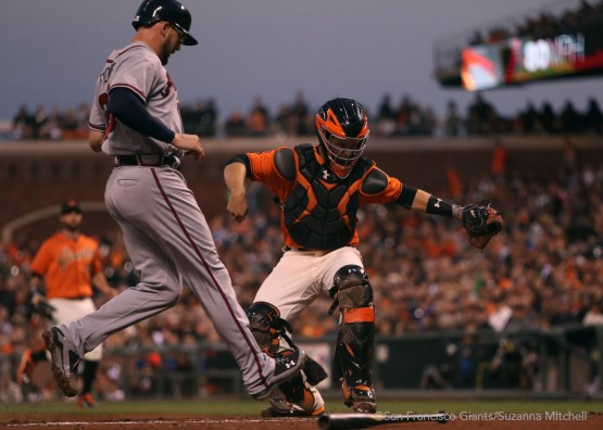 Buster Posey tags out Tyler Flowers at home plate during the second inning.