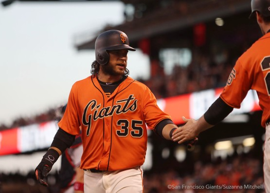Brandon Crawford gives a high five after scoring on a double hit by Joe Panik in the first inning.