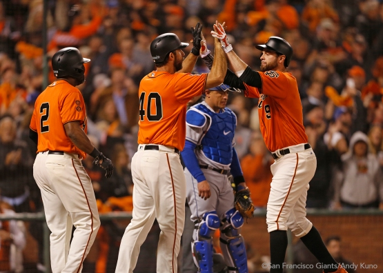 Denard Span and Madison Bumgarner high five Brandon Belt after scoring on a home run he hit in the sixth inning.