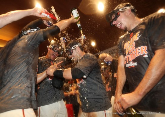 Javier Lopez, Buster Posey and Derek Law spray champagne and beer in the clubhouse.