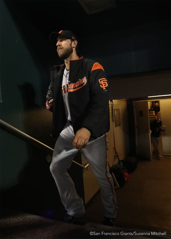 Madison Bumgarner enters the dugout to begin warming up for the game.