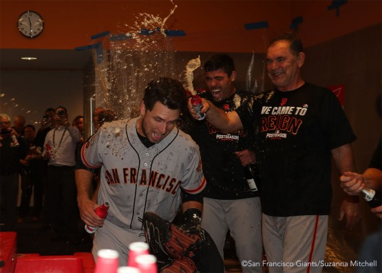 Buster Posey, Matt Moore and Bruce Bochy celebrate in the clubhouse.