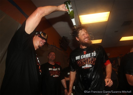 Derek Law and Hunter Pence celebrate in the clubhouse.