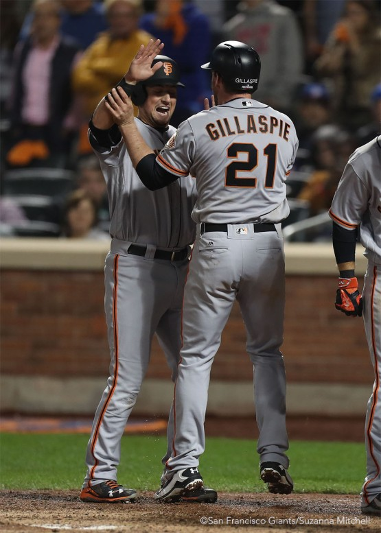 Joe Panik high fives Conor Gillaspie after scoring on the home run he hit in the ninth inning.