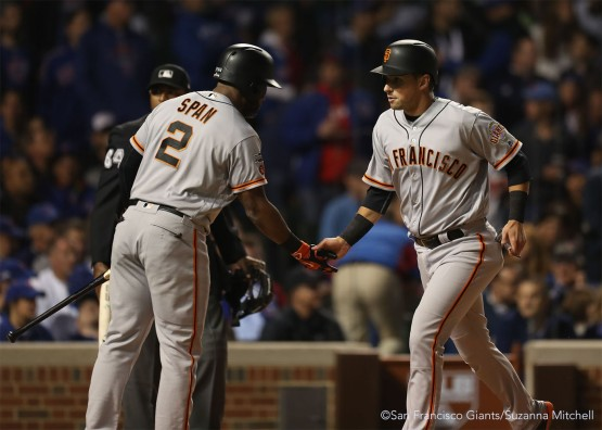 Joe Panik high fives Denard Span after scoring on a double hit by Gregor Blanco in the third inning.