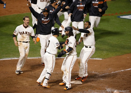 Brandon Crawford is greeted at home plate as he scores the winning run in the thirteenth inning.