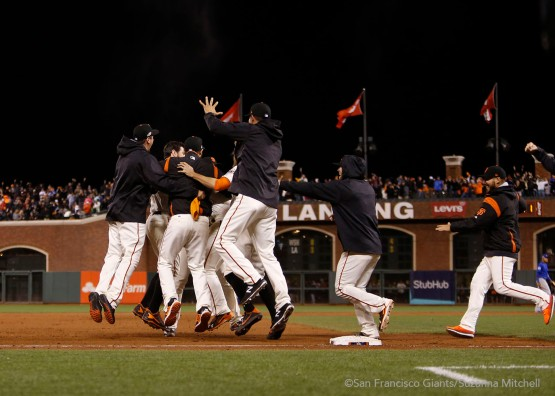 The team celebrates after Joe Panik doubled in the thirteenth inning to win the game.