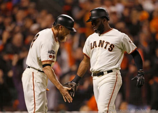 Hunter Pence high fives Denard Span after he scored on a single hit by Buster Posey in the third inning.
