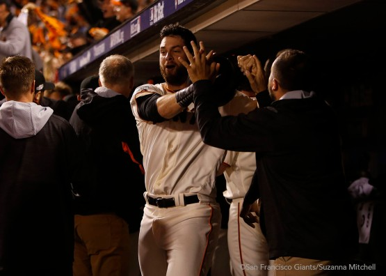Brandon Belt celebrates after scoring on a triple hit by Conor Gillaspie in the eighth inning.